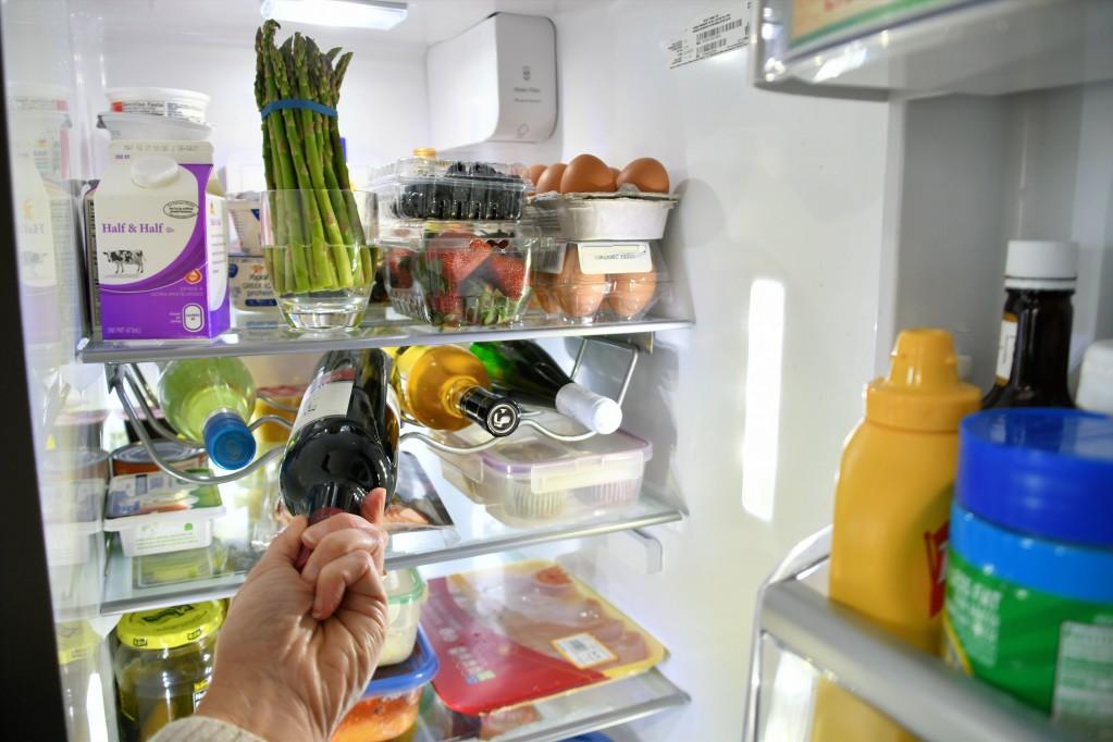 Photo d'un frigo illustrant comment conserver une bouteille de vin blanc ouverte à l'abris de la chaleur.
